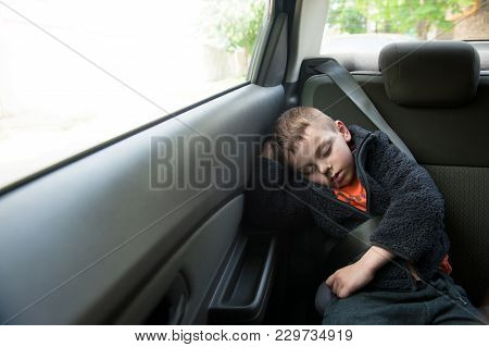 Sleeping Boy Sitting In Car In Back Seat With Seat Belt