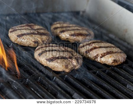 Four Chicken Meat Burger Steaks On The Grill With Flames. Cooking Chicken Grilling Or Bbq Or Barbecu
