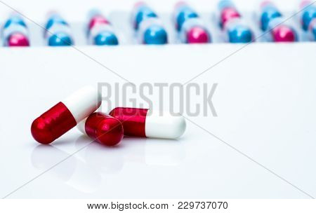 Red-white Antibiotic Capsule Pills On Pills Pack Blurred Background With Copy Space For Text. Antibi
