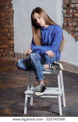 Stylish Model Child. Beautiful Teenager Girl Wearing A Blue Sweater, Jeans, Sneakers. Fashion Pose M