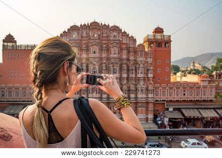 Back View Of Beautiful Young Woman Taking Phone Picture Of Hawa Mahal In Jaipur, Rajastan. Travel Co