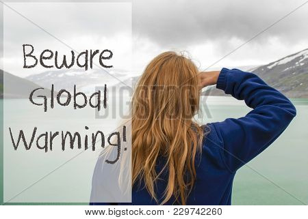 English Text Beware Global Warming. Caucasian Woman Enjoys The View To A Glacier In Norway. Lake Or