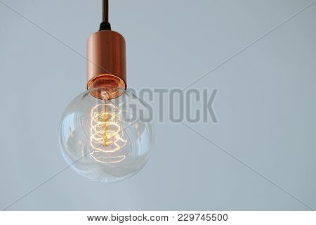 Vintage Filament Lamp With Coil Shape Light Hanging From The Ceiling Of White Background