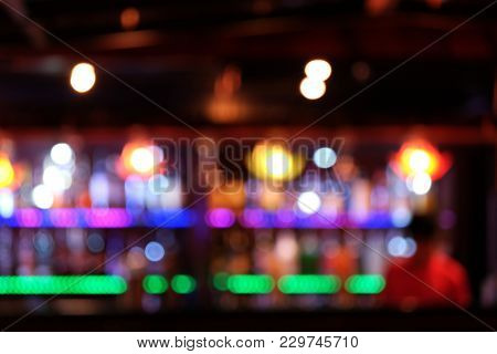 Blurry Colorful Bottles Of Whisky On Shelf Of A Bar And Bartender In Red Suite