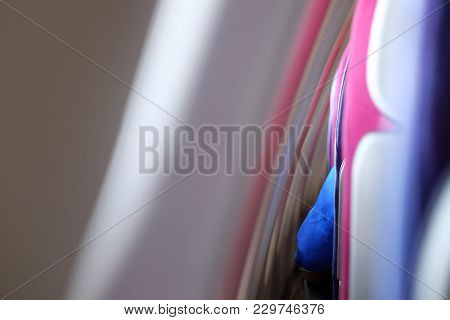Blue sleeve of passenger at the gap between the window seat and the windows of the airplane