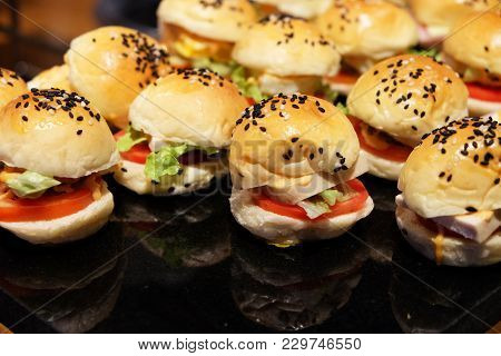 Many Little Size Of Ham Cheese Burgers On The Black Shiny Plate