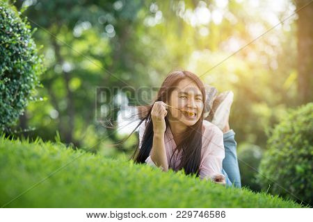 Relaxed Young Beautiful Woman With Smiling Face At The Park. Time To Relax After Work. Horizontal.bl