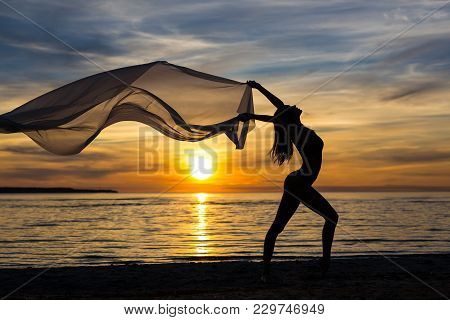 Freedom Concept - Silhouette Of Slim Woman Dancing With Scarf On The Beach At Sunset