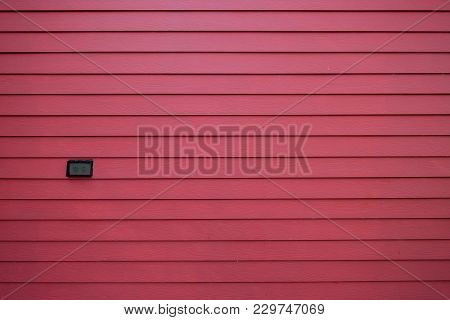 Light Switch With Rain Cover On The Pastel Red Wooden Wall In Front Of House