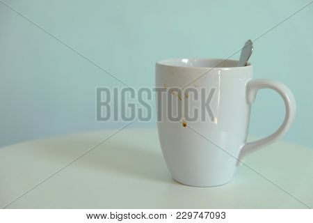 White Ceramic Coffee Cup With Stains On Round Table With Light Blue Background