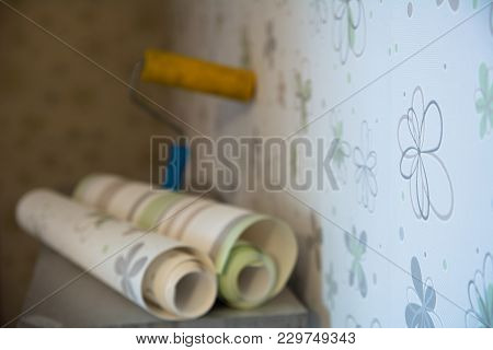 Two Rolls Of Wallpaper And A Roller Lie Against