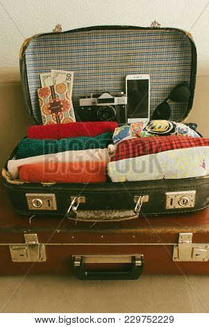 Open Vintage Leather Travel Valises Or Old Suitcase With Clothes, Passport, Camera And Sunglasses Fo