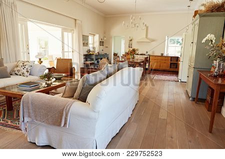 Interior Of A Living Room With A Sofa In A Country Style Residential Home With The Kitchen In The Ba