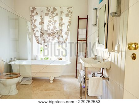 Interior Of A Bright Country Style Bathroom With A Basin, Toilet And Claw Foot Bathtub In A Resident