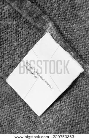 Content Clothes Label In English And Russian Languages On Grey Knitted Background