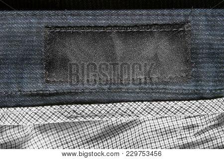 Black Blank Textile Clothes Label On Textile Background Closeup