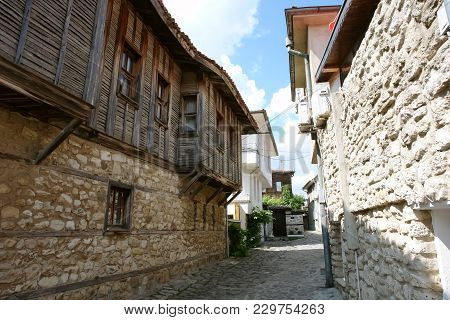 View Of A Narrow Street With Traditional Bulgarian Wooden Houses In Old Nessebar.