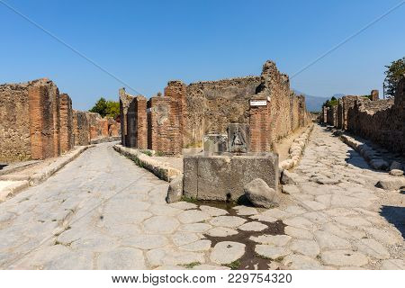 An Ancient Cobbled Street In The Ruins Of Pompeii, Italy. Roman Town Destroyed By Vesuvius Volcano.