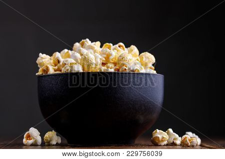 Popcorn In A Ceramic Bowl On A Wooden Background.