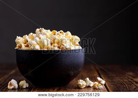 Popcorn In A Ceramic Bowl And Scattered On A Wooden Background.