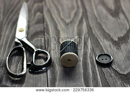 On A Black Wooden Stench, Close-up, Scissors Spool Of Thread With A Needle.