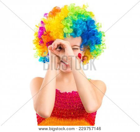 Cute little girl in colourful clown loooking through her hands like binocular, isolated on white backgrond