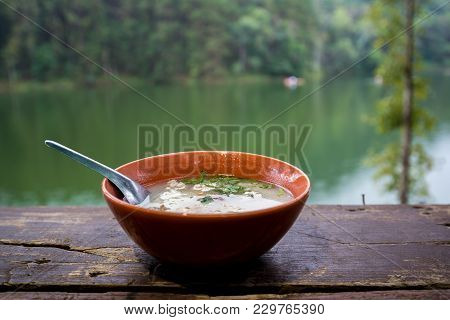 Boiled Rice With Pork And Vegetable In Black Bowl On Wooden Table With River View, Countryside Of Th