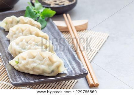 Steamed Korean Dumplings Mandu With Chicken Meat And Vegetables On A Black Plate, Horizontal, Copy S