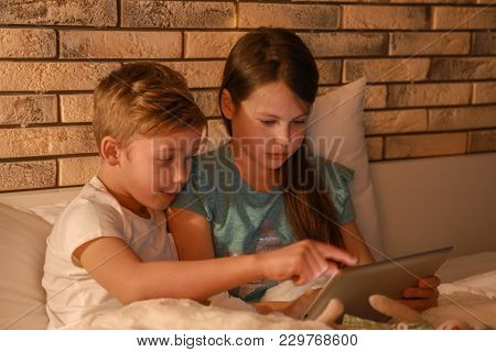 Cute little brother and sister reading bedtime story from tablet computer in evening