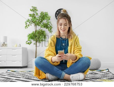Young woman in yellow cardigan using smartphone indoors
