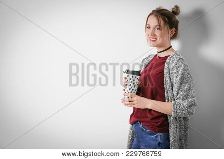 Young woman in warm cardigan on light background