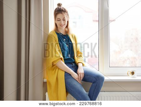 Young woman in yellow cardigan near window indoors