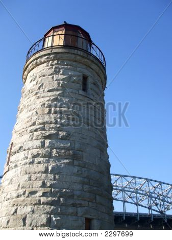 Old Stone Lighthouse And Modern Bridge