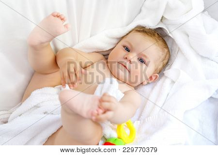 Cute Little Baby Playing With Toy Rattle And Own Feet After Taking Bath. Adorable Beautiful Girl Wra