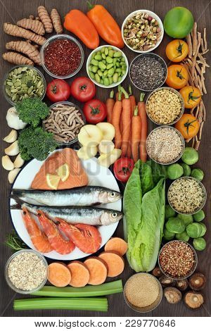 Health food concept with fresh seafood, vegetables, fruit, seeds, grains, cereals, herbs and spices with foods high in omega 3 fatty acids, antioxidants, anthocyanins, fibre, minerals and vitamins.