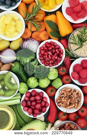 Healthy lifestyle food concept with fresh vegetables, fruit, herbs, grains and nuts. Foods very high in antioxidants, omega 3, anthocyanins, minerals and vitamins.