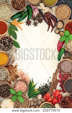 Herb and spice abstract background border with fresh and dried herbs and spices on parchment paper and rustic wood. Top view.