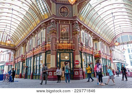 London, UK - 5th June 2017: Tourists and shoppers mingle in the colourful interior of Leadenhall Market, London. There has been a market on this site since the 14th century.
