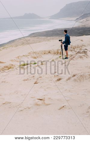 Photographer With Camera In Desert Admitting Unique Landscape Of Sand Dunes Volcanic Cliffs On The A
