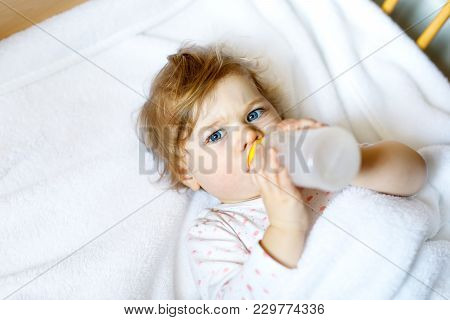 Cute Little Baby Girl Holding Bottle With Formula Mild And Drinking. Child In Baby Cot Bed Before Sl