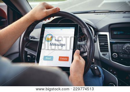 A Young Man With A Tablet In His Hand At The Wheel Of The Car.