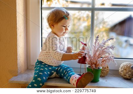 Happy Adorable Cute Baby Girl Sitting Near Window And Looking Outside On Snow On Winter Or Spring Da