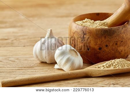 Beautiful Kitchen Still Life Wooden Mortar Full Of Grind Spicies And Pestle With Garlic And Flat Coo