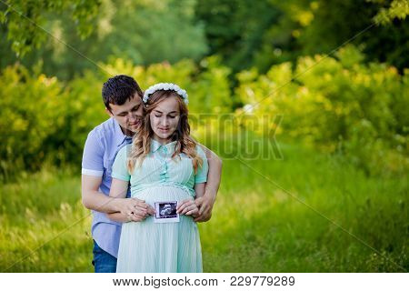 Happy Couple Are Holding Ultrasound Scan Of Their Baby On The Nature.