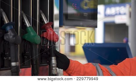 Oil, Fuel Nozzles Hang On The Machine In The Petrol Station. Clip. Close-up Of A Men's Hand Using A