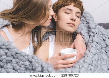 Young Lesbian Couple With Cup Of Coffee Embracing Under Knitted Wool Blanket