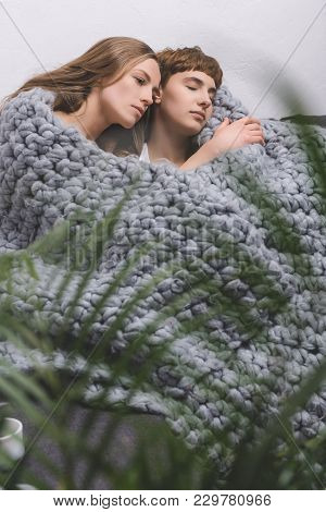 Young Lesbian Couple Sitting Under Knitted Wool Blanket Together