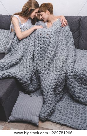 Young Lesbian Couple Cuddling Under Knitted Wool Blanket
