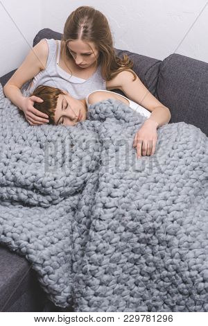 Young Lesbian Couple Spending Time Together Under Knitted Wool Blanket On Couch