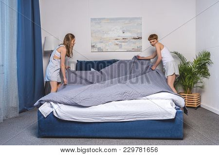 Lesbian Couple Covering Up Bed In Morning